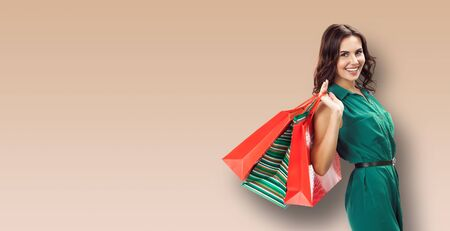 Shopping woman. Happy excited girl in green dress, holding bags, brown color background. Copy space for some slogan, advertising or text. Consumerism and sales ad concept. Banner composition.
