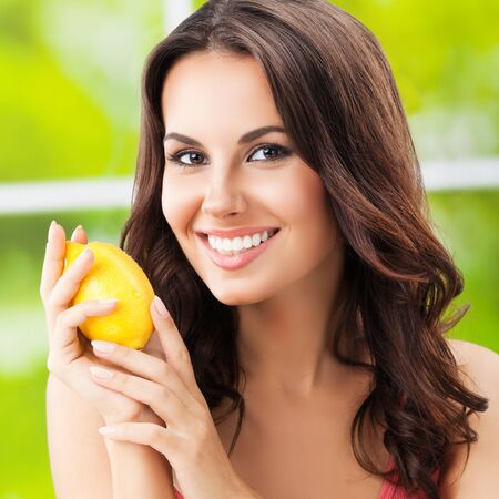 Young happy smiling beautiful woman with lemon, outdoors