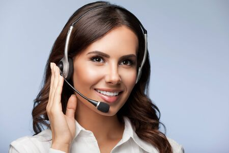 Portrait of support female phone operator in headset, over grey background. Consulting and assistance service call center.