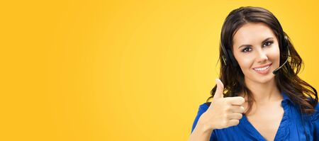 Call center service. Customer support phone sales operator showing thumb up hand sign like gesture, copy space area for some text or slogan, on yellow orange color background. Young woman in headset.