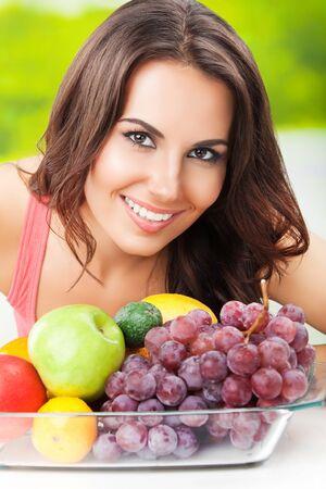 Joven mujer atractiva sonriente feliz con plato de frutas, al aire libre
