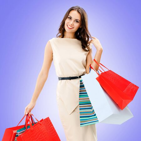 Shopping woman. Portrait of happy smiling girl holding red bag, over violet color background. Consumerism, sales and shopaholic concept picture. Square composition.