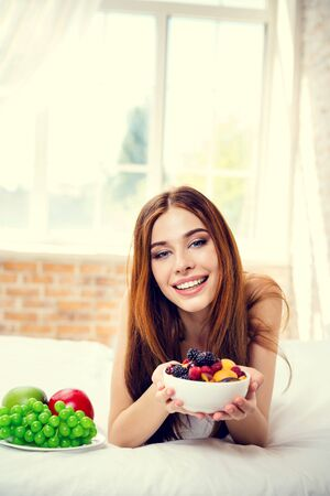 Young happy smiling girl with plate of fruits, indoors. Beauty and dieting concept. Weight lossing, by healthy eating. 免版税图像