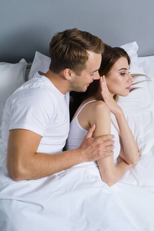 Unhappy young couple on the bed in bedroom. Caucasian models - in love crisis, relationship, frustrated concept shot. Imagens