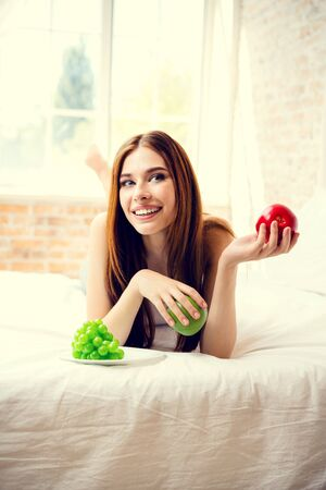 Young happy smiling girl with plate of fruits, indoors. Beauty and dieting concept. Weight lossing, by healthy eating. Фото со стока