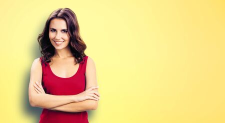Portrait photo - young smiling woman in casual red clothing, in crossed arms pose, over yellow background. Happy girl at studio. Brunette Model with long dark hair posing at studio picture. Banco de Imagens
