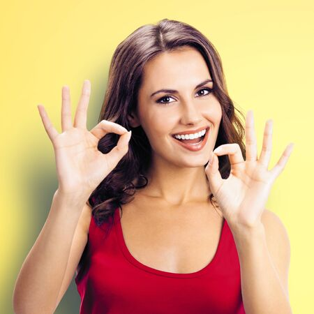 Portrait of young happy smiling beautiful woman in red casual clothing, showing okay gesture, or zero hand sign, over yellow color wall background. Girl in red dress. Brunette excited model at studio. Square composition.