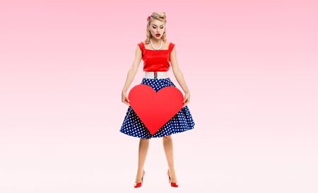 Full body of woman holding heart symbol, dressed in pin-up style dress with polka dot, isolated over pink color background. Caucasian blond model posing in retro fashion and vintage concept studio sho 写真素材