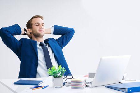Entspannender oder träumender Geschäftsmann mit Händen hinter dem Kopf, im blauen Anzug, der mit Laptop-Computer im Büro arbeitet. Erfolg im Geschäfts-, Job- und Bildungskonzept.