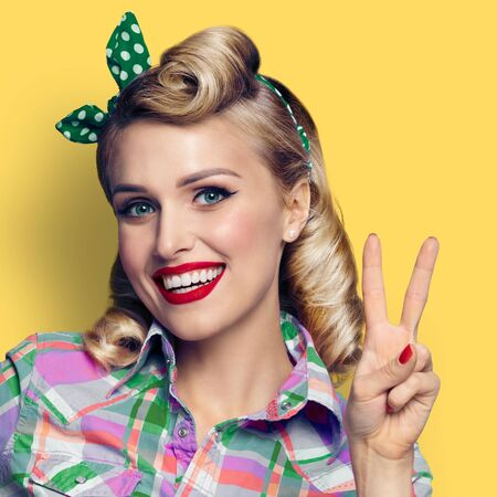 Pin up girl. Excited happy woman showing two fingers or victory gesture hand sign. Retro fashion and vintage concept. Yellow color studio background. Square composition.