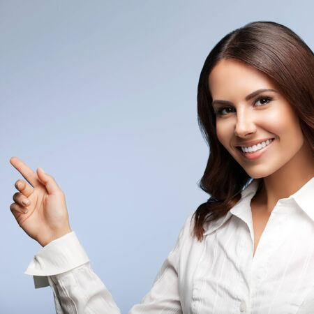Portrait of happy smiling young cheerful businesswoman, showing something or blank copyspace area for slogan or text message, against grey color background
