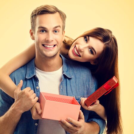 Square composition picture of happy couple opening gift box, close to each other and looking at camera with smile, over yellow background. Love, relationship, dating, flirting, lovers, romantic concept.