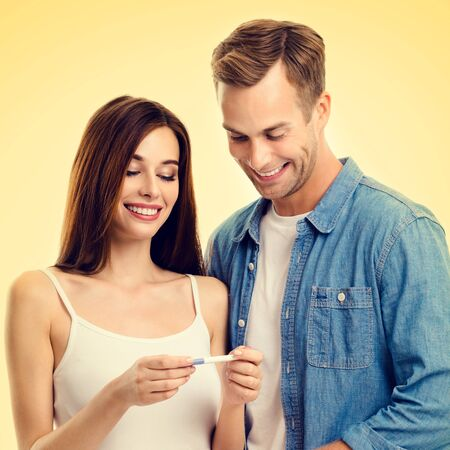 Square composition picture of young amorous happy couple, finding out results of a pregnancy test, over yellow background. Love, relationship, dating, happy lovers, family concept. Фото со стока