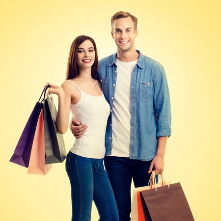 Square composition picture of happy couple with shopping bags, standing close to each other and looking at camera with smile, over yellow background. Love, holiday sales, shop, retail, consumer concept.