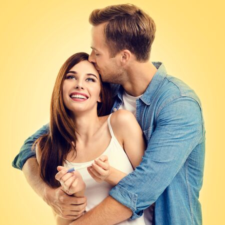 Square composition picture of young amorous happy couple, finding out results of a pregnancy test, over yellow background. Love, relationship, happy lovers, family concept.