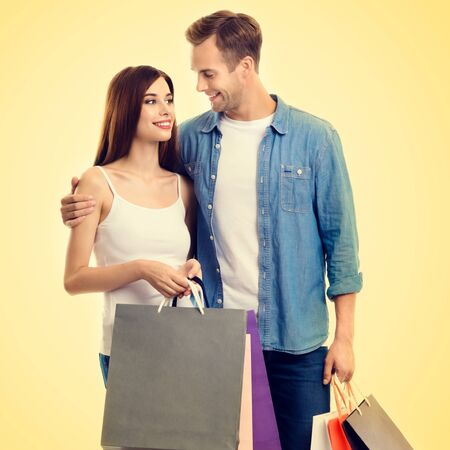Square composition picture of happy couple with shopping bags, standing close and looking to each other with smile, over yellow background. Love, holiday sales, shop, retail, consumer concept.