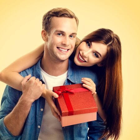 Square composition picture of happy couple with gift box, close to each other and looking at camera with smile, over yellow background. Love, relationship, dating, flirting, lovers, romantic concept.