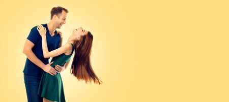 Hugging or dancing happy excited couple, looking at each other, with smile, over yellow color background. Love, relationship, dating, flirting, lovers, romantic studio concept picture. Copy space for some slogan, advertising or text.