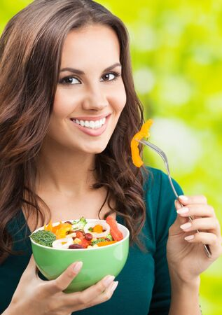 Portrait of happy smiling young woman with vegetarian vegetable salad, outdoors. Healthy eating, beauty and dieting concept.