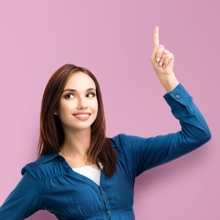 Happy smiling looking up young woman in casual smart blue clothing, showing something or copyspace for text or slogan, isolated over pink color background. Square composition.