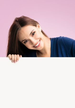 Portrait of happy smiling young woman in blue casual smart clothing, showing empty blank signboard with copy space area for text or slogan, isolated over pink color background