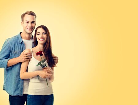 Portrait picture of young happy couple with flower, close to each other and looking at camera with smile. Caucasian models in love, relationship, dating, flirting, lovers, romantic concept. Copy space.