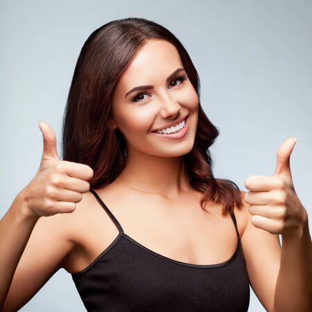 Portrait of cheerful smiling young woman showing thumb up hand sign gesture, isolated over bright grey color studio background, square composition Stock Photo