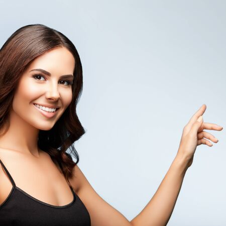 Woman in black casual clothing, showing something or blank copyspace area for slogan or text message, isolated over bright grey color studio background, square composition