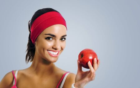Portrait of young african american woman in red sportswear with apple, isolated against grey color studio background. Women fitness concept picture. Stock Photo