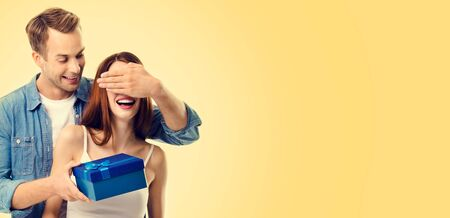 Photo of happy excited young couple with gift box, close eyes, with smile, over yellow color background. Caucasian models in love, relationship, dating, flirting, romantic concept image. Copy space. Фото со стока
