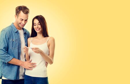 Photo of young lovely happy excited couple, finding out results of a pregnancy test, over yellow color background. Caucasian models - in love, relationship, planning of maternity concept picture. Фото со стока