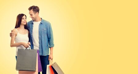 Photo of happy lovely couple with shopping bags, looking at each other, with copy space for some slogan or advertising text, over yellow color background. Man and woman - holidays sales, shopping concept.