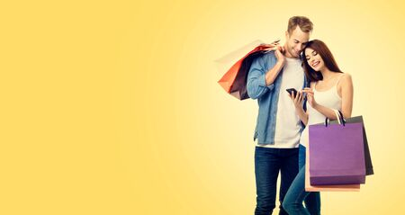 Photo of happy smiling young lovely couple with shopping bags, and smartphone, over yellow color backround. Copy space for some slogan or advertising text. Caucasian models - online shopping concept. 스톡 콘텐츠 - 130119018