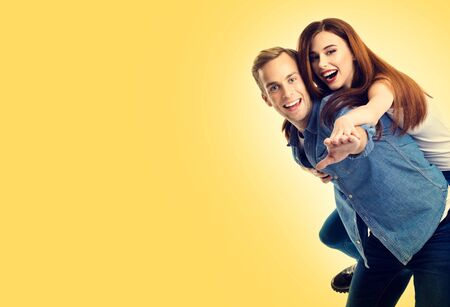 Portrait picture of playful happy excited young lovely couple, over yellow color background. Love, relationship, dating, flirting, lovers, romantic concept. Copy space for some text, advertising or slogan.