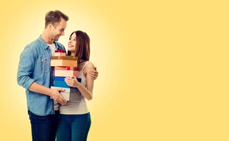Portrait photo of lovely couple with gift box, close to each other, with smile, over yellow color background. Caucasian models in love, relationship, dating, flirting, romantic concept image. Copy space.