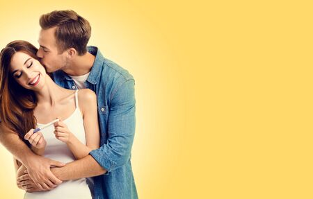 Photo of young lovely happy kissing couple, finding out results of a pregnancy test, over yellow color background. Caucasian models - in love, relationship, planning of maternity concept picture.