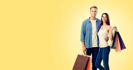 Body photo of happy young lovely couple with shopping bags, with copy space for some slogan or advertising text, over yellow color background. Man and woman - holidays sales, shopping concept studio picture. Фото со стока