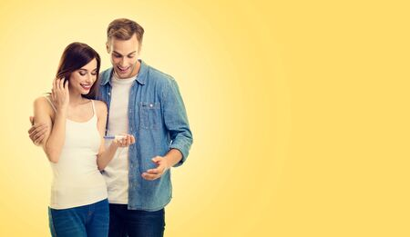 Photo of happy excited lovely couple, finding out results of a pregnancy test, over yellow color background. Caucasian models - in love, relationship, planning of maternity concept picture. Copy space.