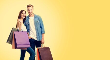 Body photo of happy young lovely couple with shopping bags, with copy space for some slogan or advertising text, over yellow color background. Man and woman - holidays sales, shopping concept studio picture. 스톡 콘텐츠 - 130119087