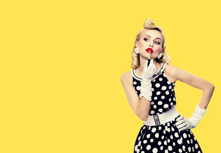 Young woman in pinup style black and white dress in polka dot, applying lipstick, with empty copy space area for some text, slogan or advertising, isolated over yellow color background. Retro fashion. Banco de Imagens