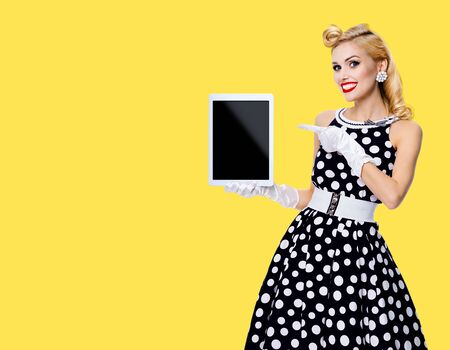 Happy smiling woman, showing empty noname tablet pc monitor, with copy space, dressed in pinup style black dress in white polka dot, isolated over yellow color background. Caucasian blond girl in retro fashion vintage concept.