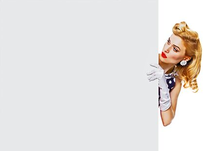 Portrait of blond girl in pin up style, showing blank signboard with copy space for some text, slogan or advertising, isolated over white background. Retro fashion. Raster vintage illustration concept. Foto de archivo - 130857196