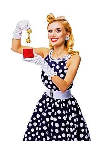Happy smiling blond woman in pin up style dress, showing keys from new house, isolated over white background. Caucasian girl in retro fashion, vintage and real estate. Raster vintage illustration concept. Foto de archivo - 130857201
