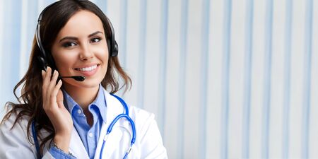 Portrait of happy smiling young doctor in headset, at office, with blank copyspace area for slogan or text. Healthcare and medicine concept picture.