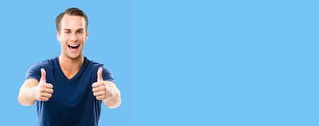 Happy excited of man in blue smart casual clothing, showing two thumb up hand gesture, over blue background. Copy space for some ad sign text or slogan. Reklamní fotografie