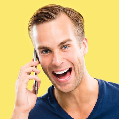 Good news! Very happy excited young man in blue casual clothing talking on smart phone, isolated over yellow color background. Mobile, cell, emotions and success concept. Square composition. Standard-Bild