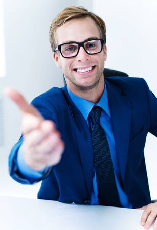 Portrait of young happy smiling confident businessman in glasses giving hand for handshake, in blue suit. Success in business, job and education concept shot. 写真素材