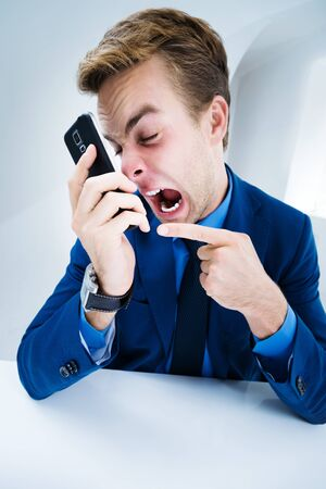 Crazy angry confident businessman creaming to cell phone Standard-Bild