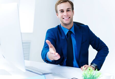 Portrait of young happy smiling attractive confident businessman giving hand for handshake, in blue suit. Success in business concept. 写真素材
