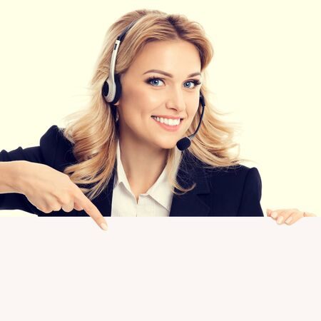 Call center. Customer support service phone operator in confident style black suit and headset showing signboard with copy space area for text or advertise slogan. Caucasian model in business success concept.